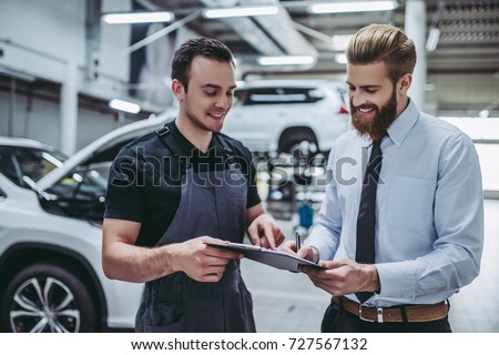 Handsome businessman and auto service mechanic are discussing the work and signing documents. Car repair and maintenance.