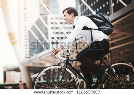 Handsome businessman caucasian wearing  white shirt with a necktie uniform in company employee using riding a bicycle work in the city, Concept healthy and ecology bike go to a work stock photo
