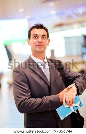 handsome businessman checking flight departure time at airport