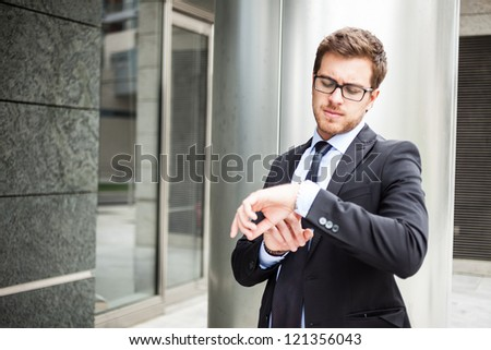Handsome businessman checking time on his watch - stock photo