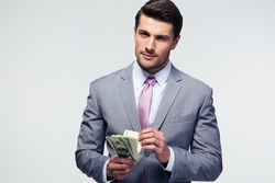 Handsome businessman counting US dollars over gray background and looking at camera