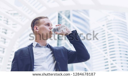 handsome businessman drinking fresh water from bottle on business district , business concept #1284678187