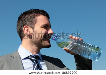 handsome businessman drinking water with bottle in blue sky