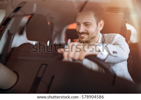 Handsome businessman driving car before buying #578904586