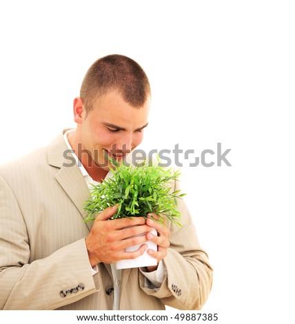 Handsome businessman enjoying his plant isolated on white