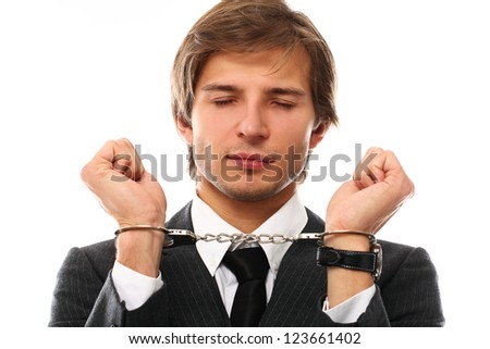 Handsome businessman hands in handcuffs over a white background
