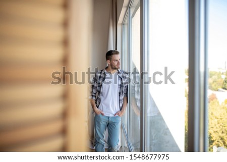 Handsome businessman. Handsome businessman wearing checked shirt standing near window in the living room