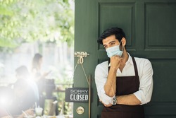 Handsome businessman has sad mood with closed sign board hanging on the door of cafe because due to viral infection. Coronavirus and quarantine concept. go out of business