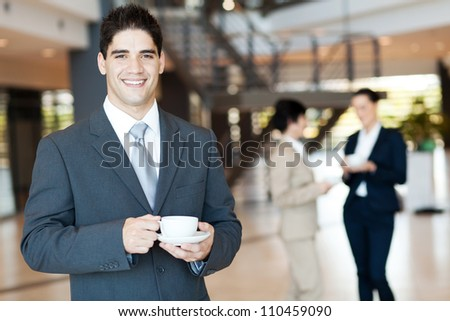 handsome businessman having coffee break in office