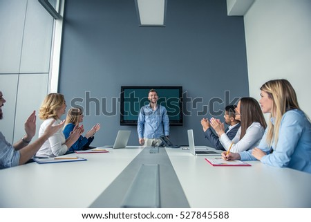 Handsome businessman holding a presentation to his team. #527845588