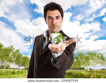Handsome businessman holding the world in his hand