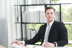 Handsome businessman in black suit wear eyeglasses and happy working with computer, notebook, laptop and smartphone on desk in modern office