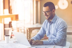 Handsome businessman in classic shirt and eyeglasses is using a laptop and smiling while working in office