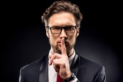 Handsome businessman in eyeglasses and suit gesturing for silence with finger isolated on black
