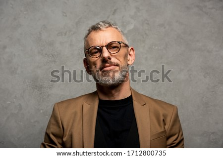 handsome businessman in glasses looking at camera on grey