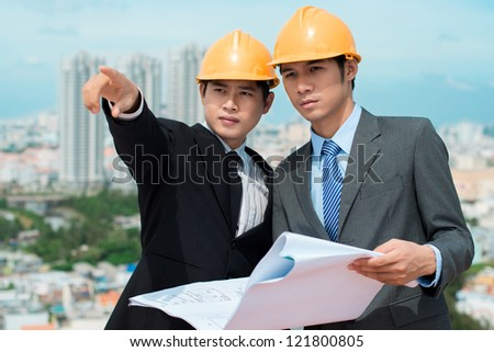 Handsome businessman in hardhat pointing in the direction of a new construction site