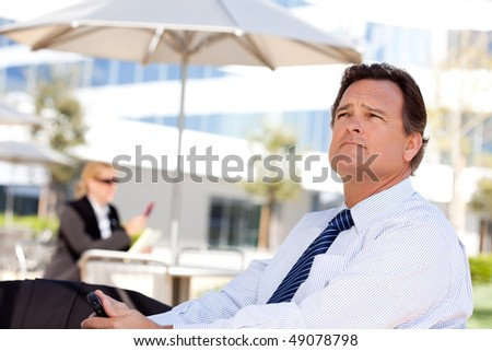 Handsome Businessman in Necktie Looks Off Into the Distance During a Break Outdoors.