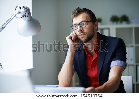 Handsome businessman in smart casual and eyeglasses speaking on the phone in office