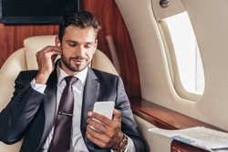 handsome businessman in suit listening music and using smartphone in private plane
