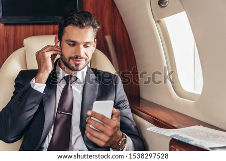 handsome businessman in suit listening music and using smartphone in private plane  ストックフォト ©