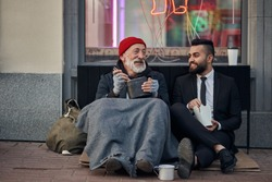 Handsome businessman in suit sitting on floor with homeless man together, listen to his story of life. Contrast people, rich and poor, but doesn't matter