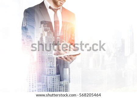 Handsome businessman in suit writing in notepad on creative city background with copy space. Young engineer taking notes. Double exposure