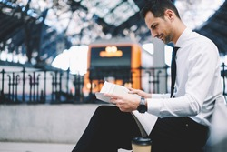 Handsome businessman in white shirt reading columns with financial news and interesting review in morning newspaper during morning routine, male stockbroker with gazzete at railway station