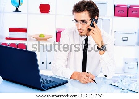 Handsome businessman is calling on his cell phone at the office.
