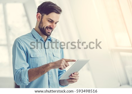 Handsome businessman is using a digital tablet and smiling while standing in office #593498516
