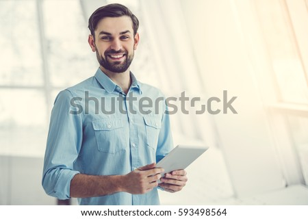 Handsome businessman is using a digital tablet, looking at camera and smiling while standing in office #593498564