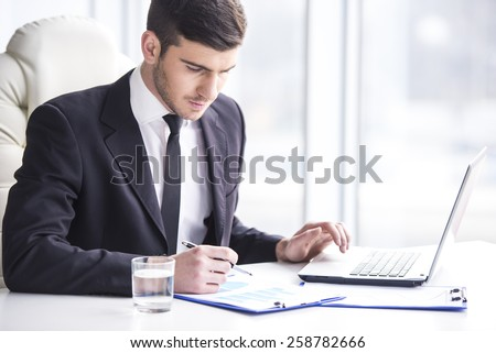 Handsome businessman is working with laptop in office.