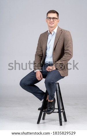 Handsome businessman isolated on light gray background. Young male in suit is sitting on chair. Full length portrait.