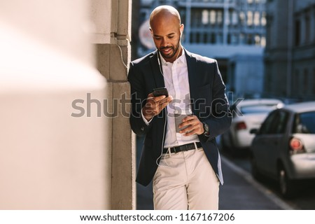 Handsome businessman leaning on a wall while standing outdoors and using smartphone. Man in suit wearing earphones looking at his mobile phone.
