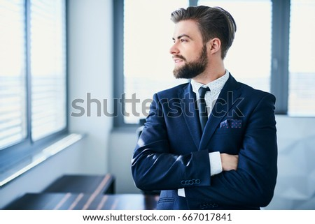 Handsome businessman looking through window while in his office #667017841