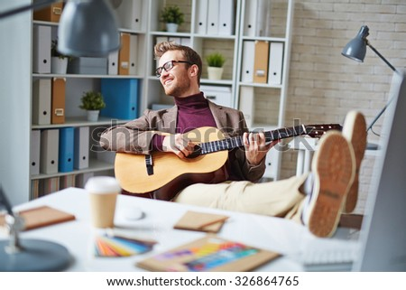 Handsome businessman playing the guitar in office after work