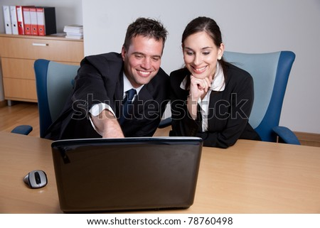 Handsome businessman pointing at the laptop screen and explaining business plan to his coworker