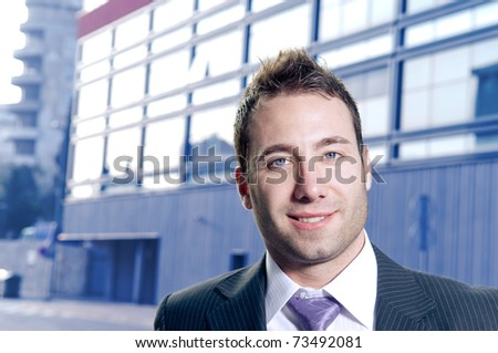 Handsome businessman portrait. Office building in the background.