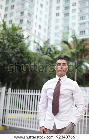 Handsome businessman posing with buildings in the background