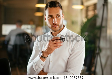 Handsome businessman posing with coffee