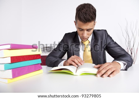 Handsome businessman reading a book in his office