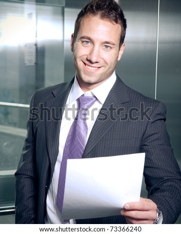 Handsome businessman reading papers and smiling