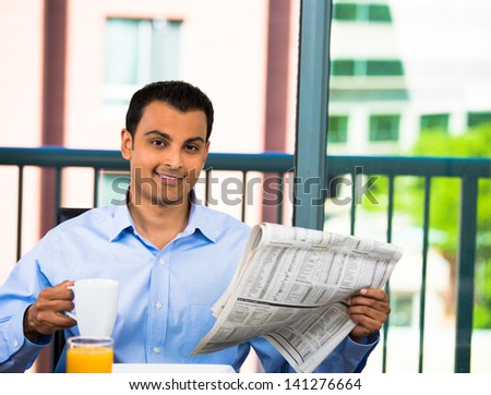 Handsome businessman reading the morning paper and enjoying a healthy breakfast