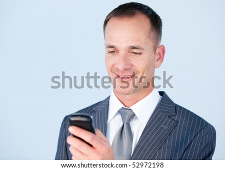 Handsome businessman sending a text with his  phone in the office