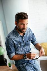 Handsome businessman sitting on a desk, writing notes. Businessman making businessplan