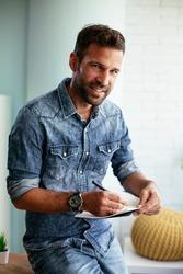 Handsome businessman sitting on a desk, writing notes. Businessman making businessplan.