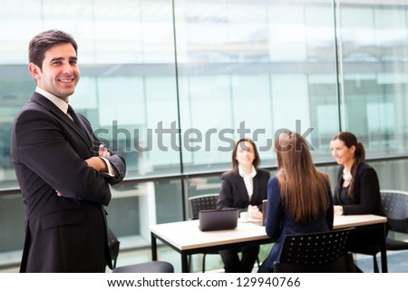 Handsome businessman smiling with his colleagues behind