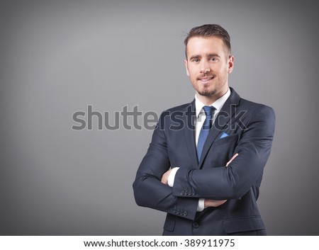 Handsome businessman standing with arms crossed on grey background