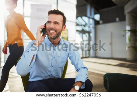 Handsome businessman talking on the phone during coffee break in a cafe #562247056