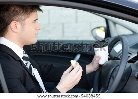 Handsome businessman talking on the phone in a car