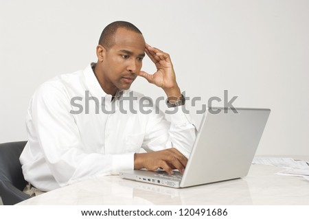 Handsome businessman using laptop while sitting at desk